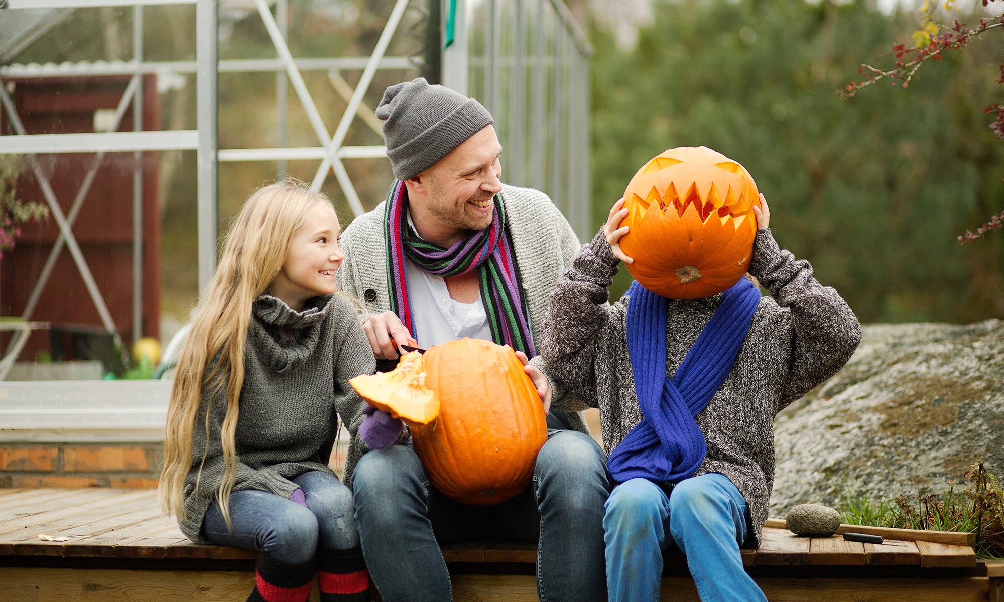 Two kids and a dad with pumpkins.